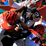 Cleveland Browns quarterback Brandon Weeden (3) is hit by Cincinnati Bengals defensive tackle Geno Atkins (97) and defensive back Jeromy Miles (45) in the first half of an NFL football game, …