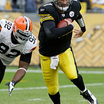 Pittsburgh Steelers quarterback Ben Roethlisberger, right, is chased out of the pocket by Cleveland Browns' Shaun Rogers (92) during the first quarter of an NFL football game in Pittsburgh,  …