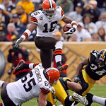 Cleveland Browns' Joshua Cribbs leaps defenders as he rushes for 18 yards after taking a direct snap from center in the first quarter of an NFL football game against the Pittsburgh Steelers, …