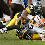 Cleveland Browns quarterback Derek Anderson, center, fumbles the ball as he is sacked by Pittsburgh Steelers linebackers James Farrior, bottom, and Lawrence Timmons in the third quarter of a …