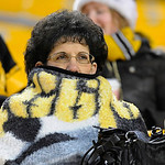 A Pittsburgh Steelers fan is wrapped up in a blanket, with temperatures in the 30s, as she watches the teams warm up for an NFL football game between the Cleveland Browns and the Pittsburgh  …