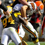 Cleveland Browns running back Peyton Hillis, right, is tackled after a short gain in the third quarter by Pittsburgh Steelers Aaron Smith, top, and Lawrence Timmons (94) during an NFL footba …