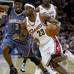 Cleveland Cavaliers' LeBron James (23) drives past Charlotte Bobcats forward Gerald Wallace (3) as Shaquille O'Neal (33) watches in the first quarter of an NBA preseason basketball game, Tue …