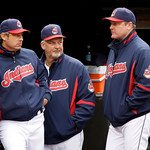 Cleveland Indians manager Eric Wedge, right, talks with hitting coach Derek Shelton, left, and pitching coach Carl Willis during the fourth inning of the first game of a baseball doubleheade …