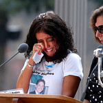 A woman wipes her eyes after reading the name of her brother, Bobby Hughes, as friends and relatives of the victims of the 9/11 terrorist attacks gather at the National September 11 Memorial …