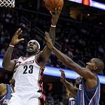 Cleveland Cavaliers' LeBron James (23) drives to the basket against Charlotte Bobcats' Raja Bell in the second quarter of a preseason NBA basketball game, Tuesday, Oct. 6, 2009, in Cleveland …